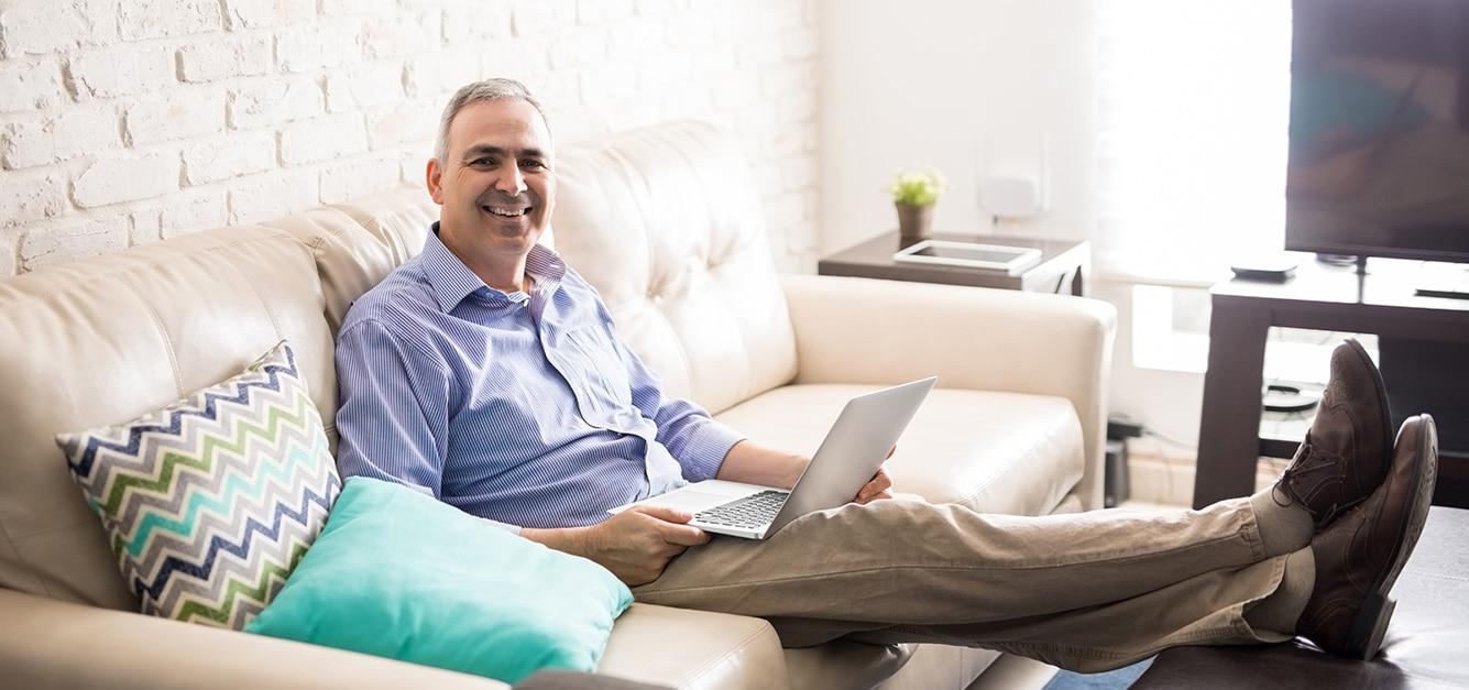 Smiling mature man working on a laptop